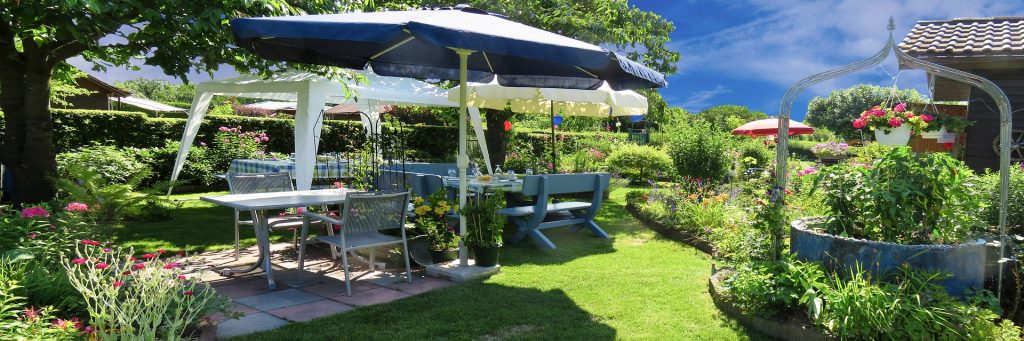 Practical and fine - big garden with flowers and tables ready for celebration