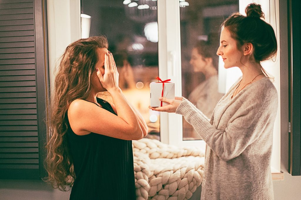 woman giving a gift to another woman
