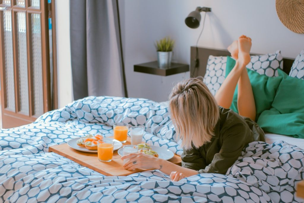 woman having breakfast on bed sheets