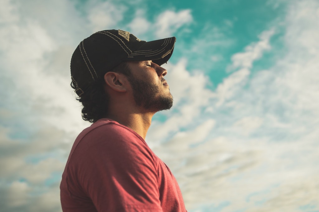 meditating man wearing black cap with eyes closed under cloudy sky