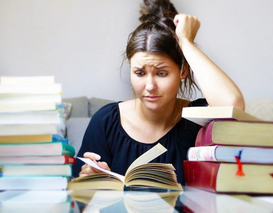 girl reading lots of books looking anxious
