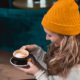 woman holding black teacup with cappuccino