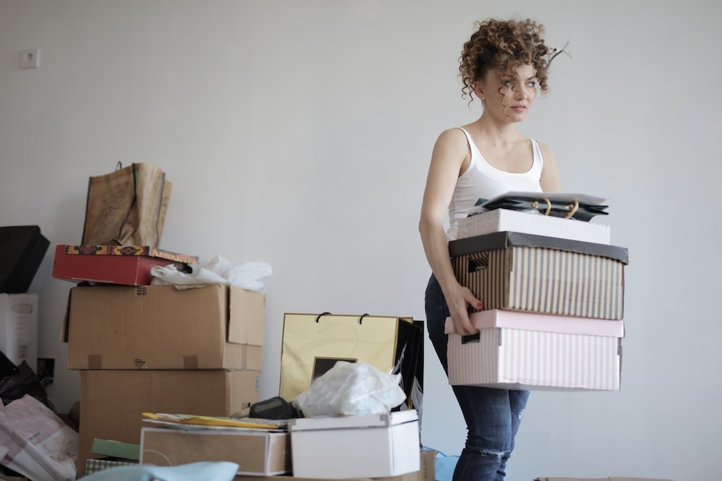 woman decluttering a house carrying boxes