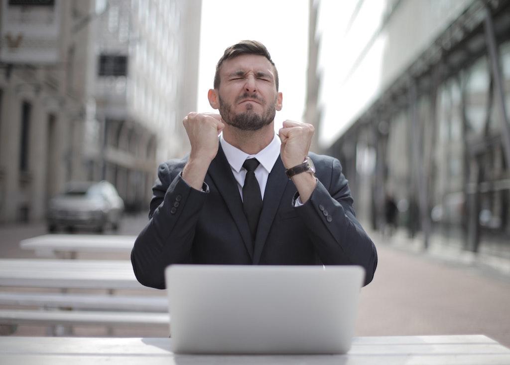 grateful man in black suit sitting on chair beside buildings
