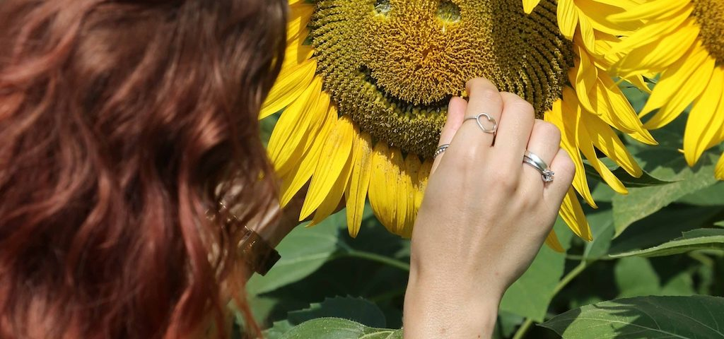 woman drawing smile on sunflower