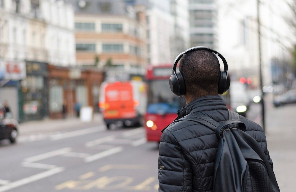 the fake commute - man with headphones walking in the city